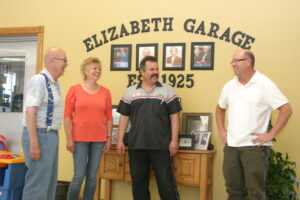 Jack Graves (left) and children, Jennifer, Jeff and Jay laugh together in the lobby of the Elizabeth Garage. A history of the establishment is on display behind them.