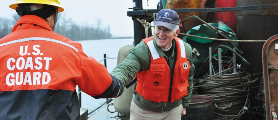 Chaplain Kempton Baldridge of Seaman's Church Institute greets a crew member aboard the U.S. Coast Guard Cutter Chippewa. The Chippewa, a 75-foot buoy tender, is responsible for working floating and shoreline aids along the Tennessee, Ohio and upper Mississippi rivers. Baldridge travels these same rivers offering support and encouragement to members of the inland merchant marine. Photo courtesy of Gregory Thorp.