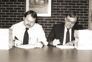 Returning money to members in the form of capital credits is one way electric cooperatives differ from investor-owned utilities. Adams Electric Cooperative Manager Roger Mohrman, right, and Accountant Chris Bennett are shown signing capital credits checks by hand in 1983.