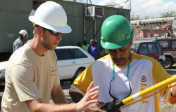 Shelby Electric Lineman Brian Chevalier explains how to use a hotstick to a Haitian lineman.