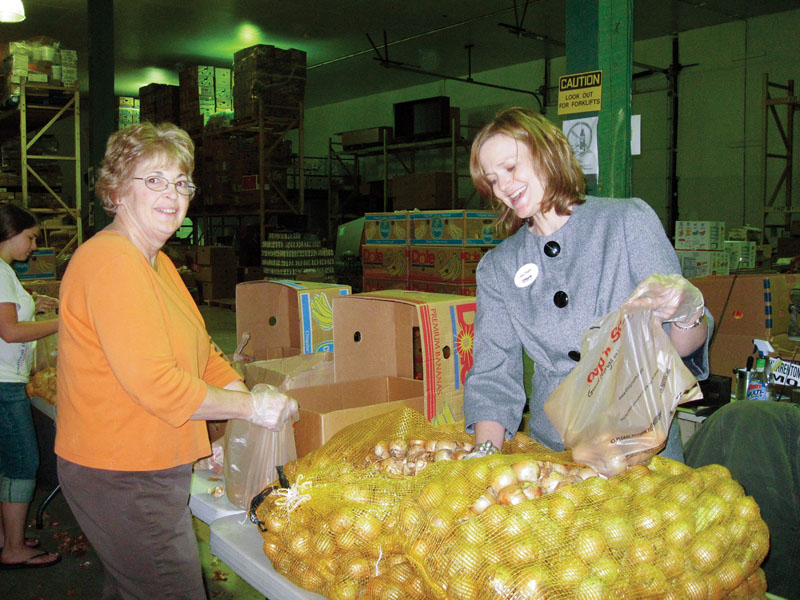 Volunteers help sort potatoes into smaller packaging.