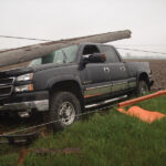 A shattered utility pole remains atop the damaged pickup truck with de-energized lines still attached.