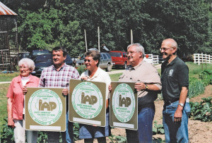 Grandmother Rita along with sons (l-r) Richard, Robert and Steven hold the new Sesquicentennial Farm signs presented to them by State Rep. Jim Sacia.