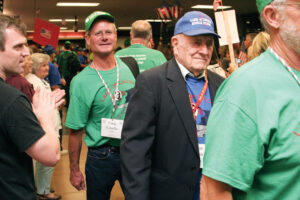 """Craig Costello (center), a volunteer for the Land of Lincoln Honor Flight, agrees with Will Rogers who said, """"We can't all be heroes. Some of us have to stand on the curb and clap as they go by."""""""