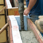 Man pouring concrete into wall molds at construction site