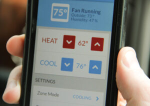 Joseph Smith, Chief Technology Officer for Prairie Power, Inc., demonstrates his new smart phone app that can control the temperature of his home via the Internet. Soon smart home apps like this will cooperate with the smart grid to help balance power supply and demand.
