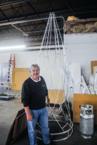 Blachere Illumination President Ronnie Brown stands next to an aluminum frame ready for lights.