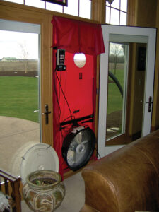 A blower door set up in the exterior door of a home.