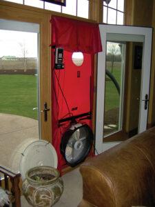 A blower door set up in the exterior door of a home.