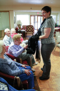 Candace Summers, Director of Education, shares a 1920s ­flapper dress in the Well Dressed Folks About Town program with ­participants at Blair House, Normal.