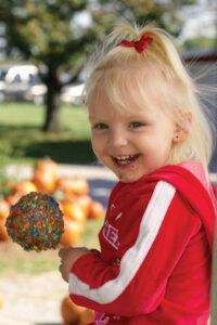 Little-girl-holding-caramel-apple