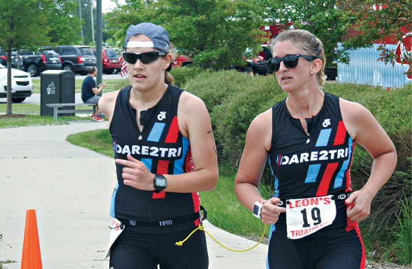 Ashley, left, and guide Lindsey Cook complete the final leg of the Leon's World's Triathlon in Hammond, Ind.