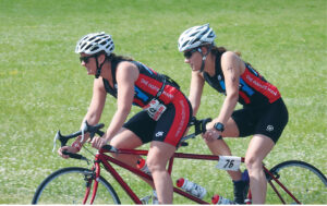 Lindsey Cook pilots the tandem bike during the second leg of the triathlon