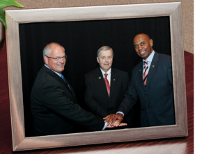 Phil Carson standing with two other NRECA board members.