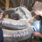 Two men inspecting air ducts