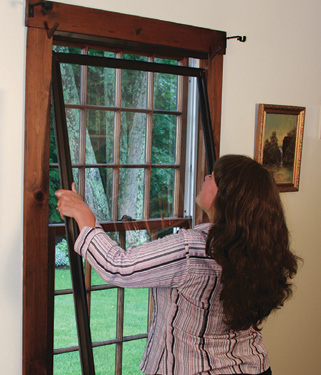 Woman installing a storm window in her house