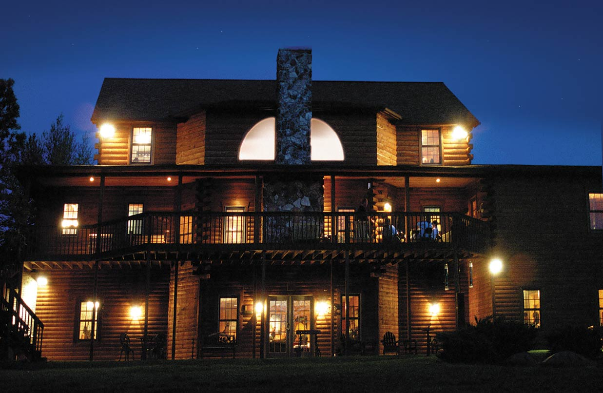 Heartland Lodge with brightly lit windows under a night sky.