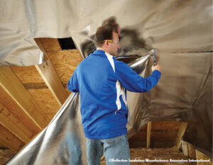 Man installing reflective foil insulation