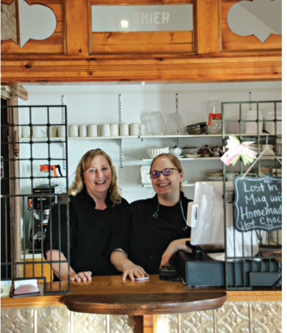 Two women at restaurant cashier station.