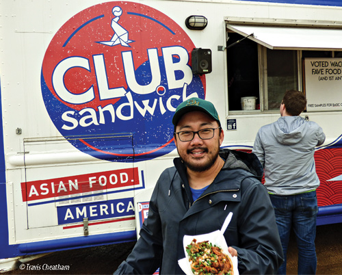 Man holding meal outside of Club Sandwich Korean American food truck.