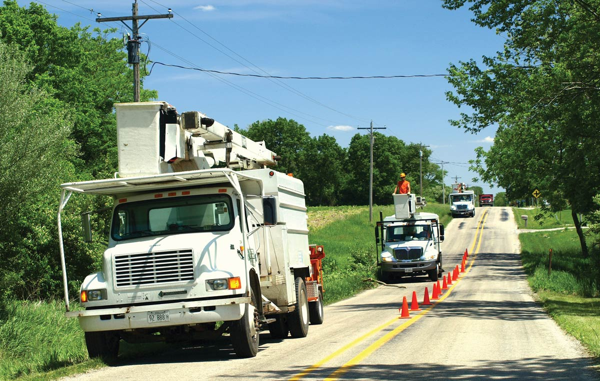 Three bucket trucks on a road with orange safety cones along the center line.