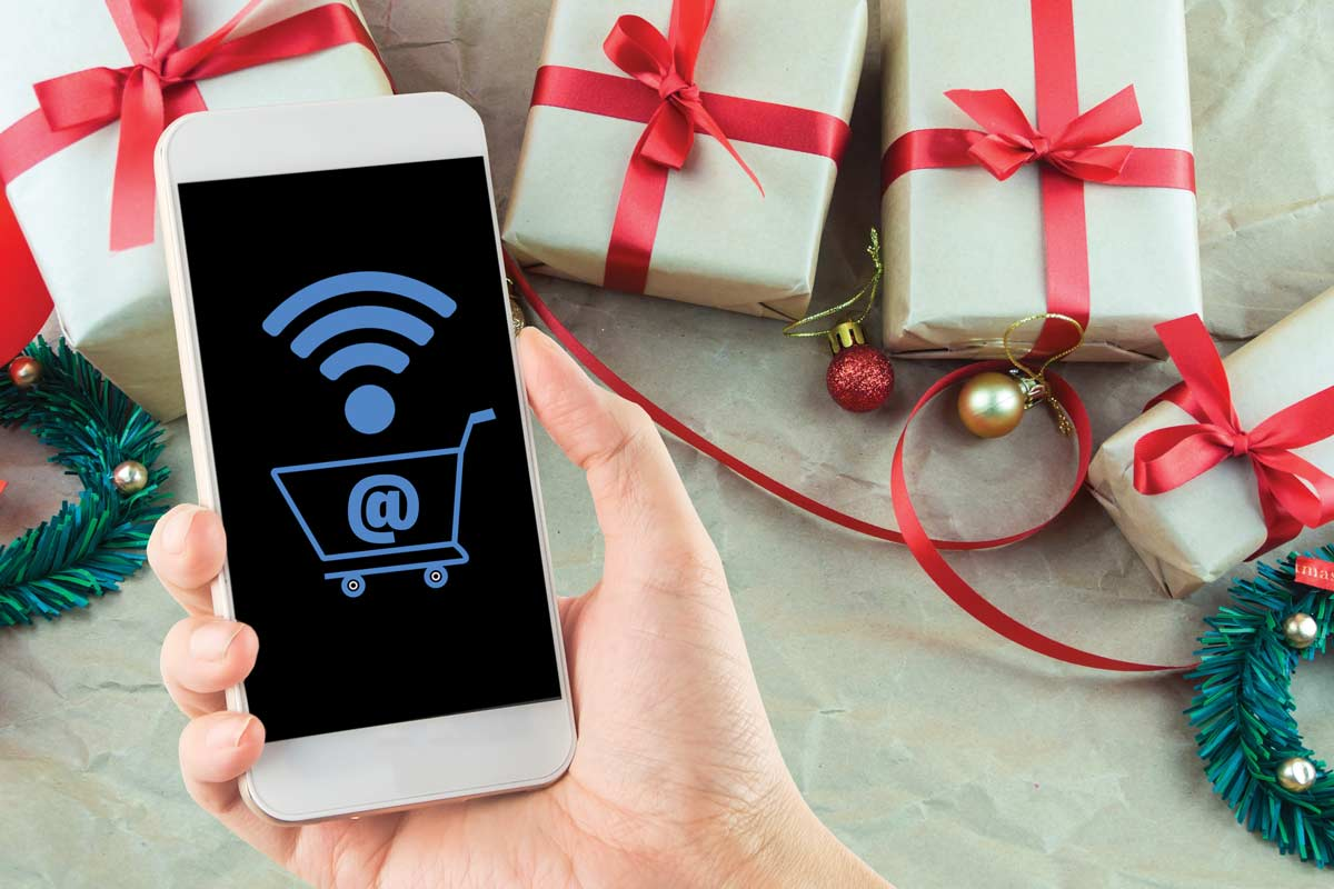 White iPhone with wifi and online shopping symbols on screen, with Christmas packages in the background.