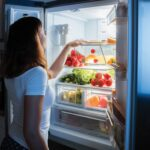 Woman looking into open refrigerator