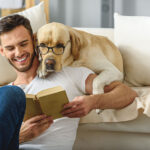 Man and dog reading book