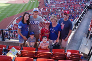 Family at the game. Some wearing cards apparel some wearing cubs.